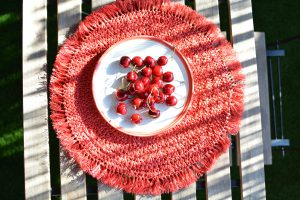 White plate filled with red cherry fruit