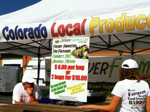A market tent with a sign reading 'Colorado Local Produce'