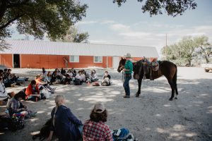 Woman stands with horse in the middle of a semicircle of schoolkids, part of Chico Basin's education program
