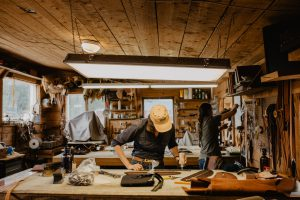 Inside the leather shop at Chico Basin, a woman is at the work table
