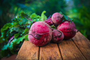 close up of red beets sitting on a wooden table